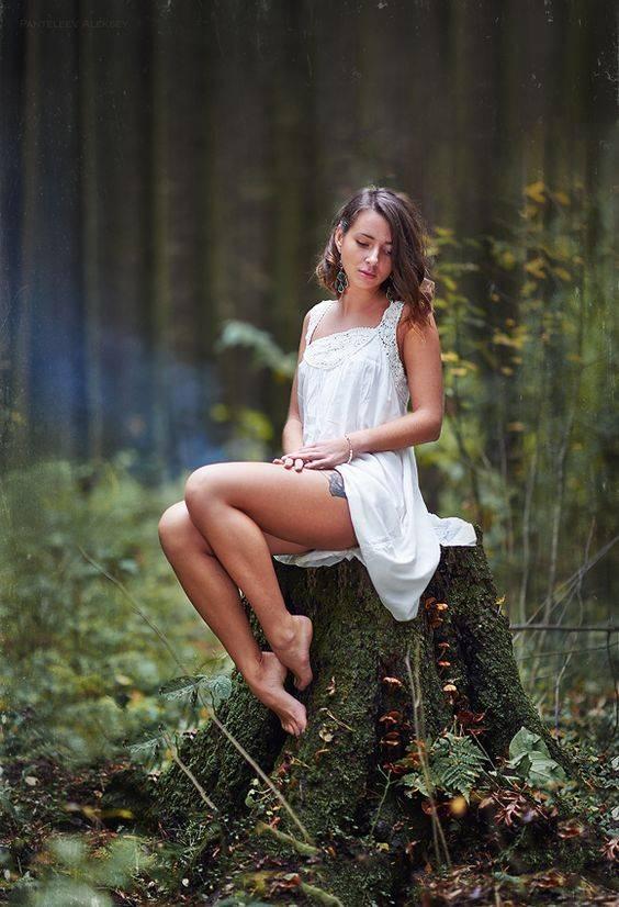 Красивая девушка-июнь сидит на пне в лесу